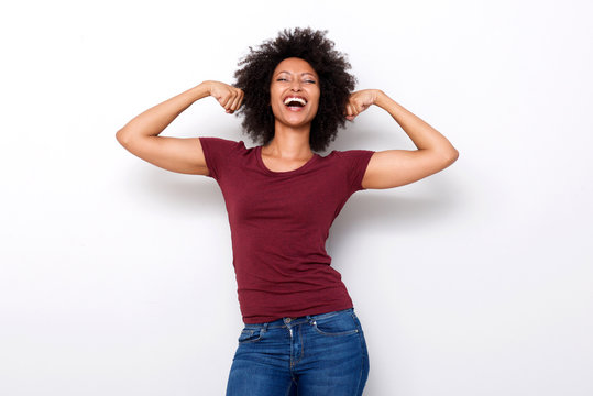 healthy young african woman flexing both arms muscles on white background