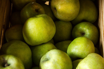 a few green yellow macro apples with shadow  in a wooden box