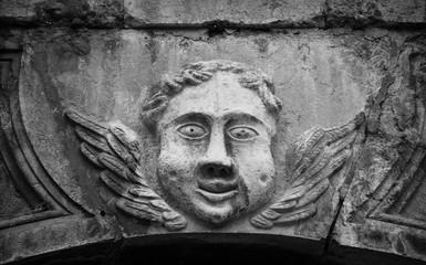Smiling face of angel on the front of Cathedral of Notre Dame of Assumption in Entraveaux (Alpes de Haute Provence, France). Black white photo.