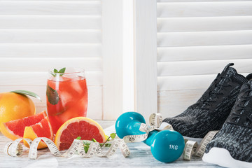 Fresh grapefruits and grapefruit juice, dumbbell and measuring tape, on rustic white wooden table opposite the blinds, fitness accessories. Concept of slimming, dieting and healthy nutrition.