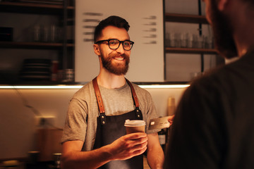A picture of bearded hipster barmen that wears glasses standing behind the bar stand and holding a cup of coffe that he did for the customeer. The barman looks happy and smiling.