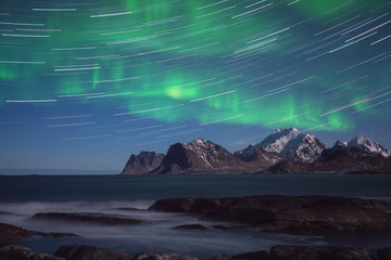 Northern lights, Aurora borealis with star trails over the rocky mountains, scenic night landscape, Lofoten Islands, Norway