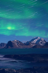 Northern lights, Aurora borealis with star trails over the rocky mountains, scenic night landscape, Lofoten Islands, Norway. Vertical image
