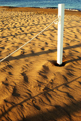 summer sea, white pole with rope on the beach at dawn