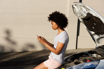 young black woman standing by broken down car and using cell phone for assistance