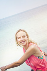 Relaxed fitness woman is happy at the beach