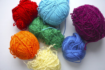 Knitting from threads of all colors of a rainbow on a white background
