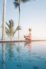 Beautiful woman practicing yoga at the pool