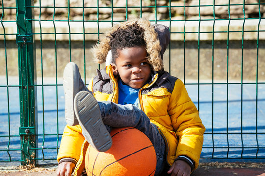 Funny little boy resting sitting on the ground with the legs on the basket ball