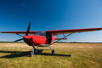 A small red light-engine aircraft with a propeller stands in the middle of a