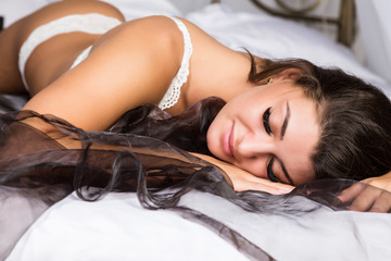 Beautiful woman in a white lingery resting on a bed