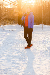 Picture of sports woman with backpack standing in winter