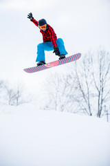 Picture of sports man with snowboard jumping in snowy resort