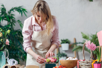 Photo of blonde florist making composition of flowers