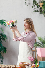 Photo of florist holding bouquet in hands at table with marmalade, marshmallow, boxes, paper