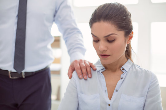 Female abuse. Nice cheerless unhappy woman sitting in the office and looking at the male hand while being sexually harassed