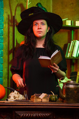 Photo of witch with book at table with pumpkin, skull