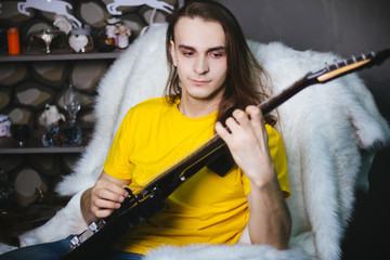 Man with long hair in yellow t-shirt, playing on electric guitar rock. Fashion studio portrait on a gray background.
