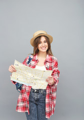 Smiling traveller girl in hat holding map and looking at camera.