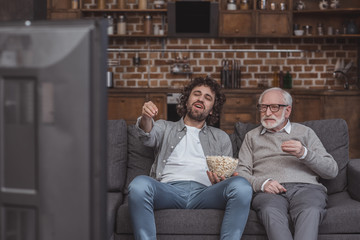 adult son and senior father watching tv on sofa at home