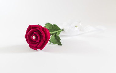 Red paper rose on white background