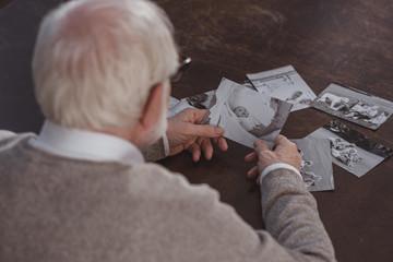 rear view of grey hair man sitting at table and looking at photos at home