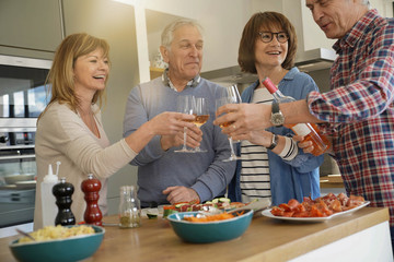 Senior people cheering with wine while preparing meal