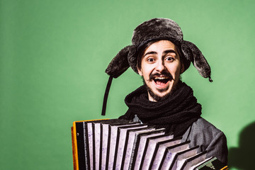 a very positive man with an accordion posing in the studio
