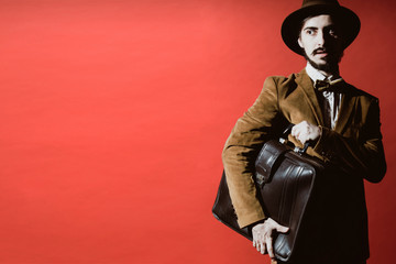man posing in studio with suitcase in hands