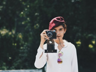 Young traveler woman holding vintage camera.