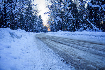 Evening winter road. Road in the forest at sunset