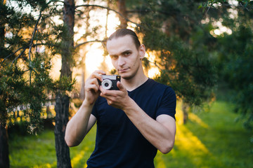 Handsome guy with a retro camera. A film camera in the hands of a young photographer. Model on the background of the park