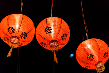 a trio of red Chinese paper lanterns all lit up for Chinese New Year