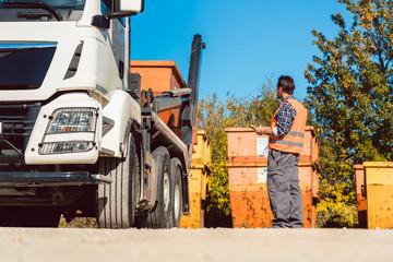 Bauarbeiter auf Baustelle lädt Bauschuttcontainer ab