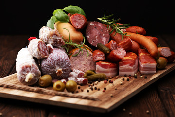Food tray with delicious salami, ham,  fresh sausages, cucumber and herbs. Meat platter