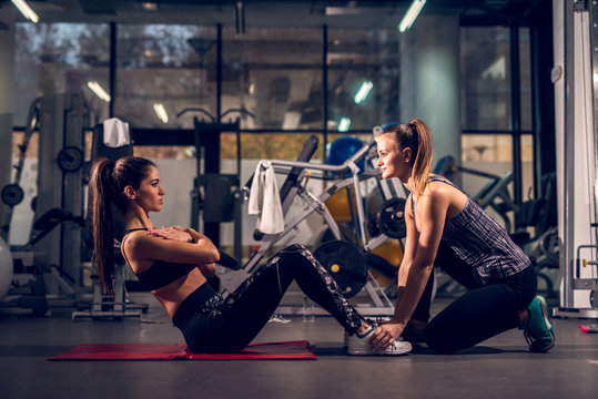 Side view of young motivated attractive healthy sporty active shape girl doing abs exercises and warming on the red mat while her young personal female trainer holding legs in the gym.