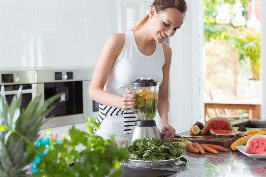 Smiling vegan woman making smoothie