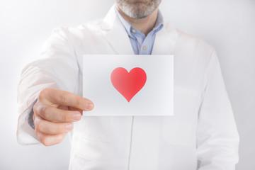 Arzt hält eine Karte mit einem Herz in der Hand