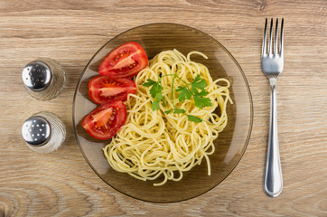 Spaghetti in plate with tomatoes, parsley, salt, pepper and fork