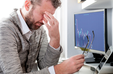 Depressed investor analyzing crisis stock market with graph on screen at home office