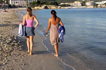 Two girls walking along the tide line on a beach in Majorca, Spain.
