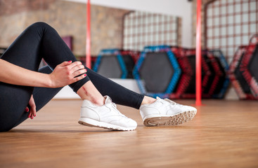 Injured woman feeling pain in her ankle at fitness gym