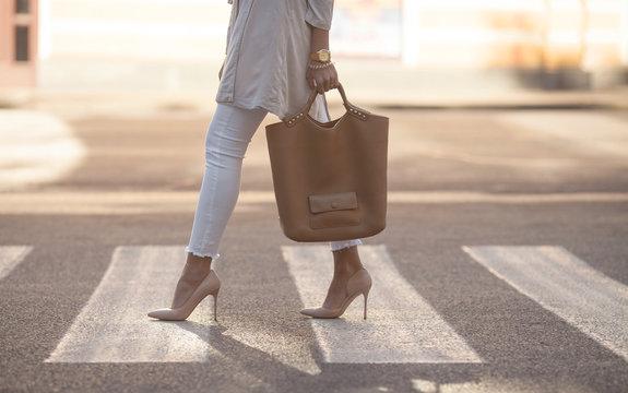 close up of woman legs walking on crosswalk. The woman is wearing shoes on high heels. Handbag in woman hand.