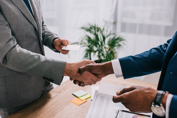 Cropped image of two businessmen shaking hands and giving visit cards to each other