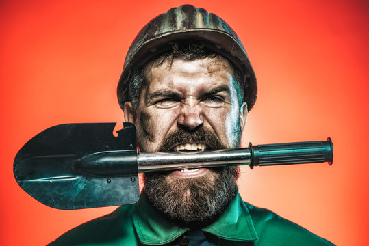 Mining and construction concept - man with angry face in protective helmet holds shovel in teeth. Bearded man wears working uniform and harthat. Man worker in helmet holds sapper shovel Military spade