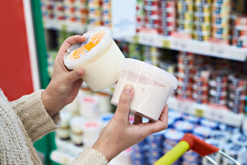 Foto op Plexiglas Zuivelproducten Buyer hands with plastic yogurt jars at grocery