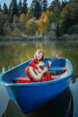 Девочка-цыганка плывет в лодке по озеру с гитарой осенью