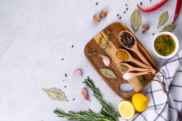 Cutting board with herbs and spices  - rosemary, garlic, salt, pepper, olive oil, lemon. Culinary background. Food flat lay.