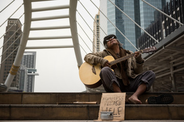 Old beggar sing and play guitar