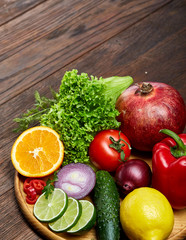 Still life of fresh organic vegetables on wooden plate over wooden background, selective focus, close-up